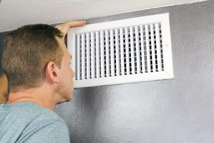 A Picture of a Man Checking Air Flow From a Vent.